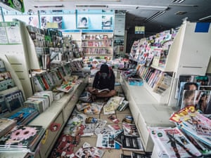 Wearing a gas mask but no other protective clothing, explorer and photographer Keow Wee Loong, 27, sits on the floor of a shop reading the magazines