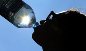 A woman drinks water on a hot day