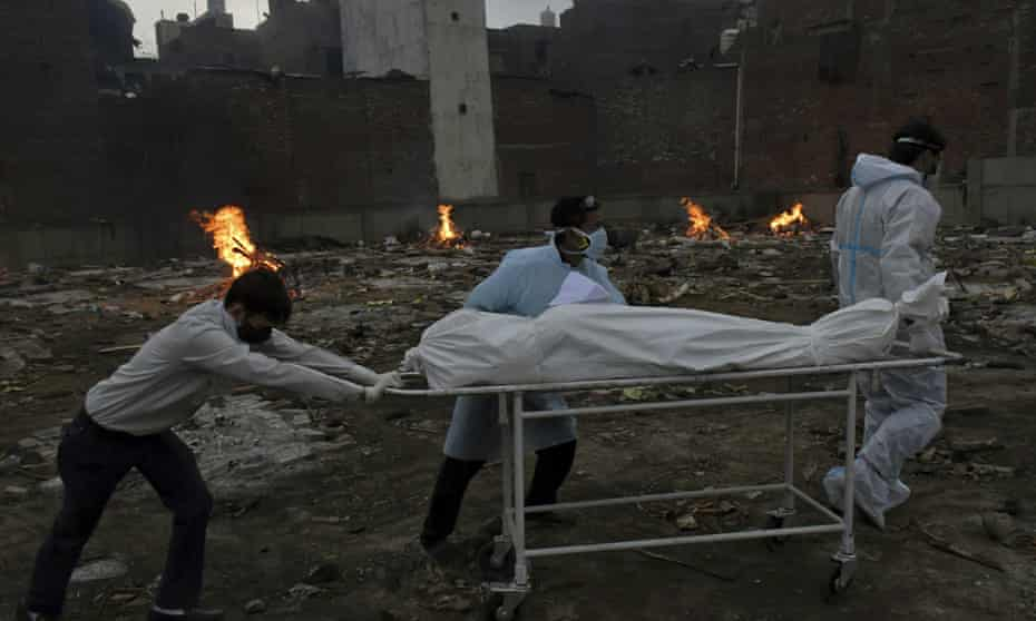 The body of a Covid-19 victim is wheeled in for cremation on Thursday on ground converted into a crematorium in Delhi