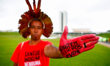 A protester shows a sign on his hand that reads 'Stop killing us', during a demonstration this year against a bill that would open lands to mining in Brazil.
