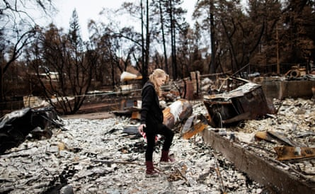 Ruth McLarty sifts through the remains of her destroyed home in Paradise, California.