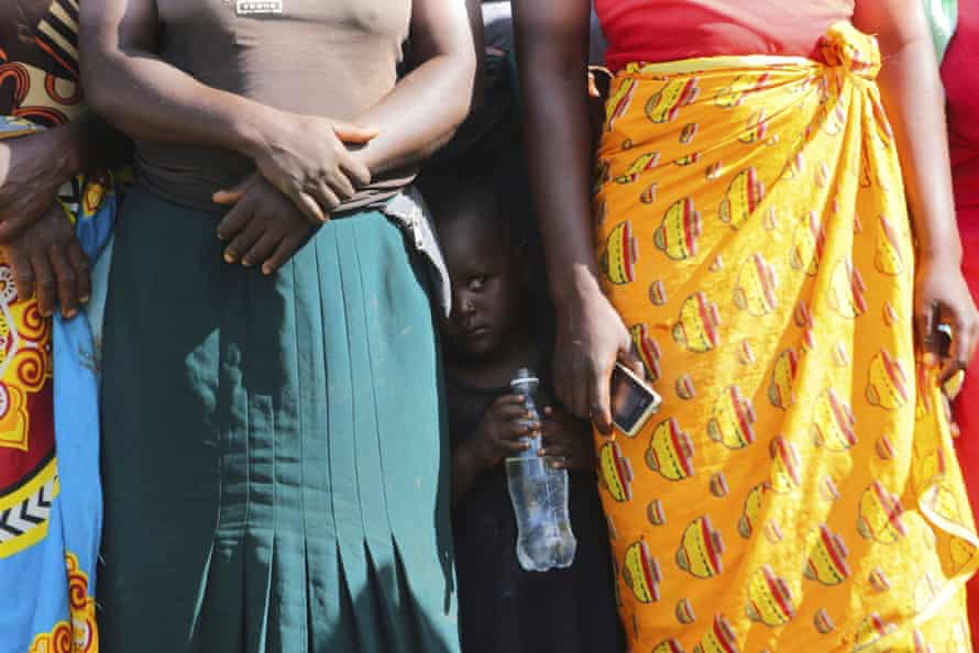 A child stands between women waiting to receive food aid, in Mudzi, Zimbabwe