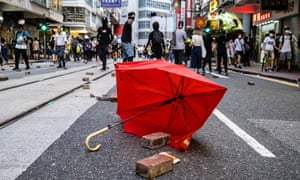 A broken umbrella with bricks lie in the road during a demonstration in Hong Kong