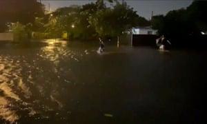 People walk in floodwaters caused by Storm Eta in Fort Lauderdale.