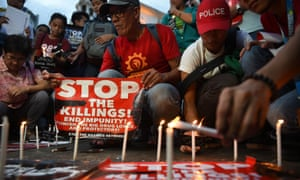Activists light candles in front of a church in Manila during a vigil for victims of extra-judicial killings in the government's drug war.