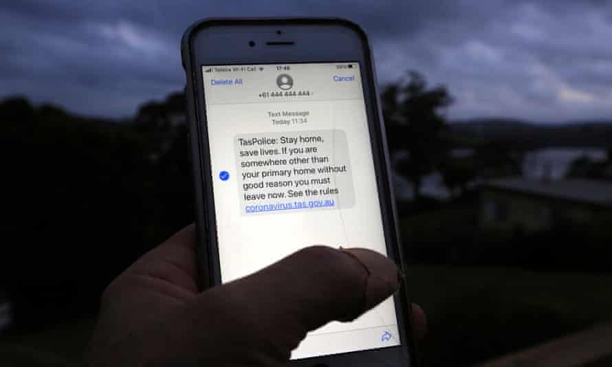 A man reads a mass emergency text message sent to Tasmanian citizens from police, near Launceston, Tasmania, Australia.