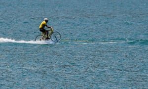 A man wearing a yellow jersey water skis on a bicycle