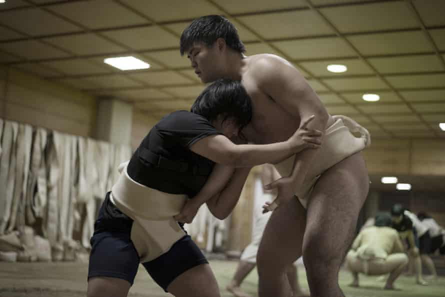 A female and a male member of the Asahi University sumo team practice against each other during their daily training.
