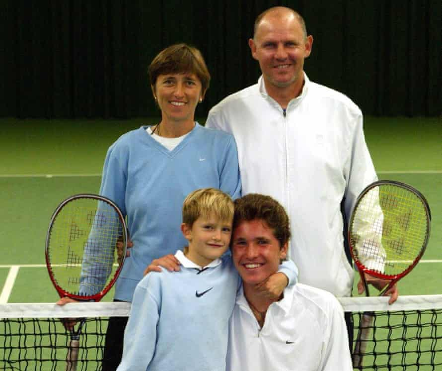 Alex Zverev as a boy with his older brother in front of a tennis net, with his parents standing behind them, the other side of the net