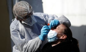 A medic wearing a protective suit gives a patient a nasal swab in Paris.
