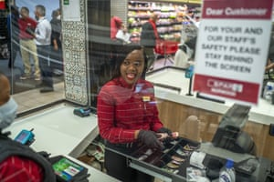 In this 30 March photograph, Zandile Mlotshwa, 21, cashier at Spar supermarket in the Norwood suburb of Johannesburg, counts her cash at the end of her shift.