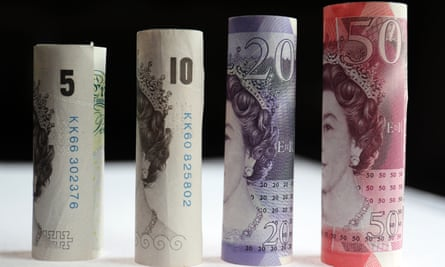 A rolled up fifty, twenty, ten, and five pound notes