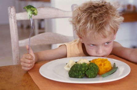 A young boy looking grumpy about having to eat vegetables