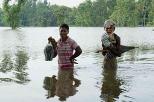 Men wade through floodwaters in Kurigram, northern Bangladesh