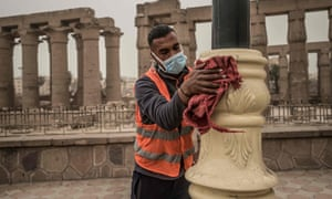 A municipality worker cleans lamp posts amid a sandstorm and coronavirus fears outside the Luxor Temple in Egypt's southern city of Luxor on 12 March.