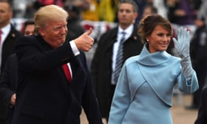 Donald Trump, wearing black, makes a thumbs-up gesture and Melania Trump, wearing a blue coat and gloves, waves