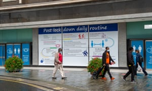 People walk past council public information signs on empty shop windows in Slough High Street, Berkshire