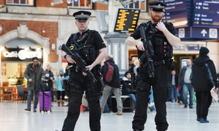 Armed police patrol a train station in London