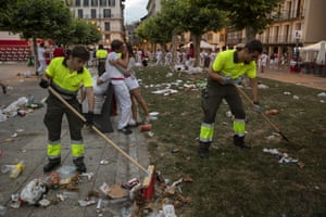 A couple kiss in the early hours as workers clean the streets of Pamplona
