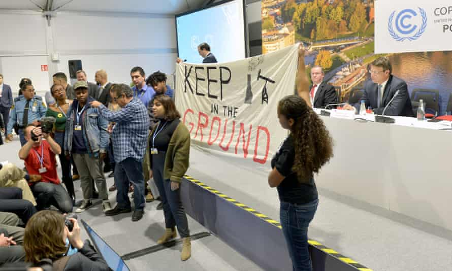 Patrick Suckling (sitting on panel right), Australia's ambassador for the environment, waits as protesters disrupt an event at the COP24 climate change summit in Katowice, Poland