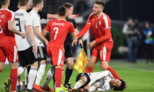 Serbia's Milan Pavkov reacts is shown a red card after fouling Germany's Leroy Sané.