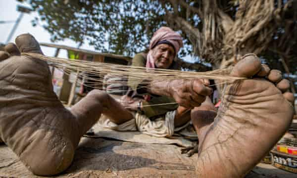 Zapatero, from the Chamar community, making thread to sew soles in Uttar Pradesh.  A job in the civil service is a way out of extreme poverty for Dalits.