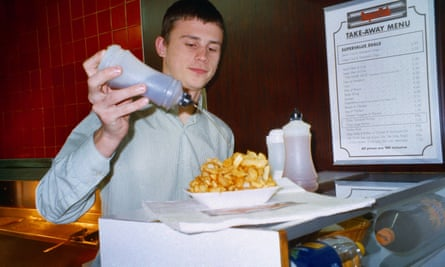 Demonstrating the traditional English meal of chips and non-brewed condiment.