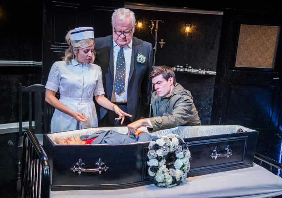 Sinead Matthews, Ian Redford and Sam Frenchum with Anah Ruddin in the coffin in Loot by Joe Orton at Park theatre, London, in 2017.