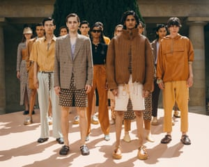 """Nanushka Sandra Sandor's fledgling menswear label showed its second collection, titled """"Come as you are"""", in a co-ed presentation. Models lounged on sculptures and furniture in a sunny courtyard. Nanushka's signature vegan leather appeared in a basket weave jacket with an oversized funnel neck and shorts. Other highlights were the bleached-lemon shorts two-piece, with straw hat, and the sunset orange suit."""