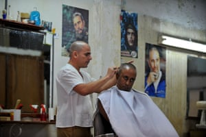 A barber works near posters of Castro and fellow Cuban revolutionary leader Che Guevara
