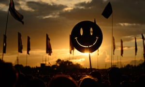 A smiley face sign is carried through the crowds as the sun sets.
