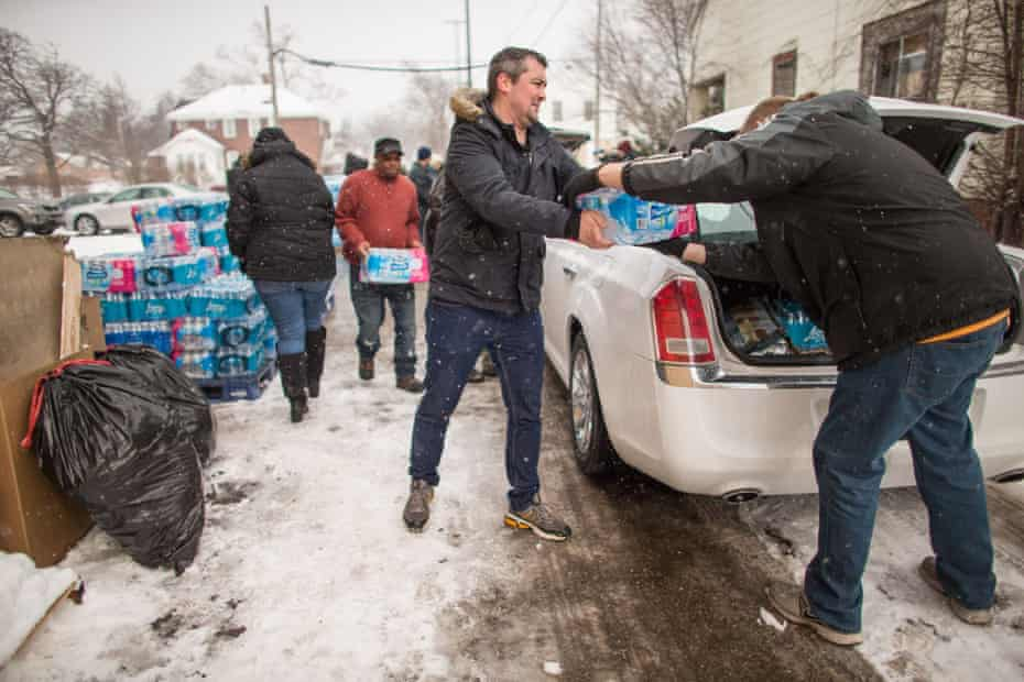 Volunteers load cases of free water into waiting vehicles at a water distribution centre at Salem Lutheran Church in Flint, Michigan in 2016.