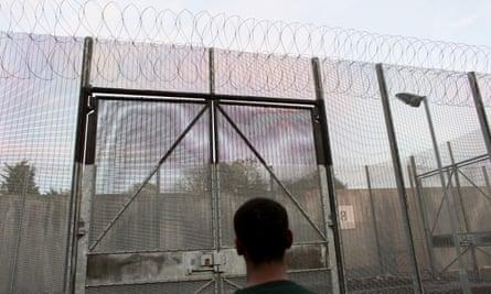 Man facing prison gates.