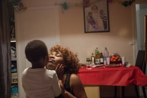 Corinne Kyoto-Sy, who works as a carer, kisses her son, Kesyah, on New Years' Eve in Bondy, Paris