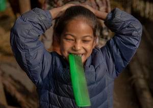 Girl smiling tying her hair with comb in mouth