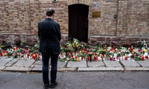 A man looks at tributes outside the synagogue in Halle, Germany