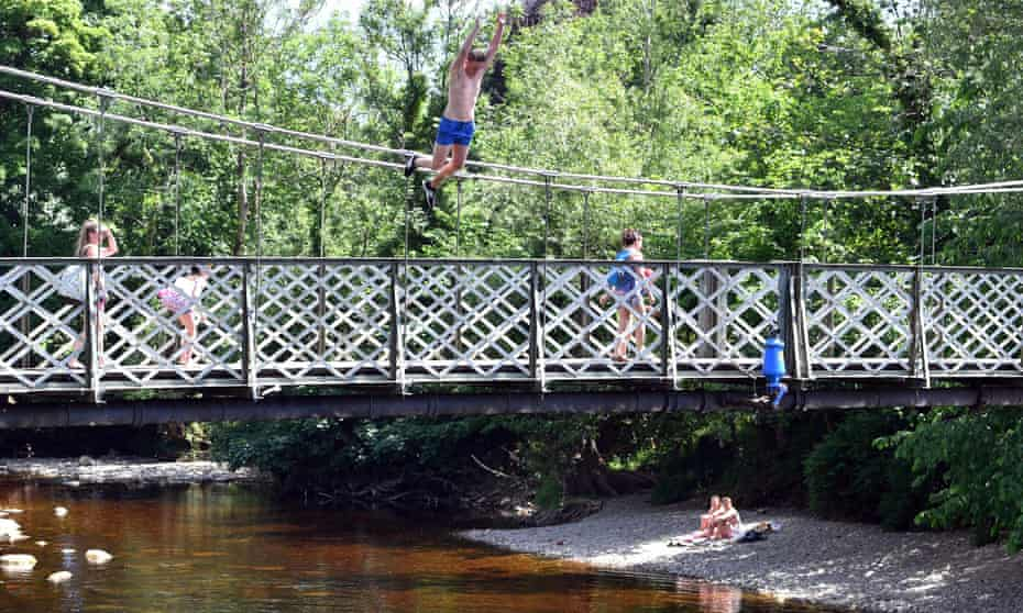 A man jumps from the suspension bridge into the Wharfe in Ilkley last month.