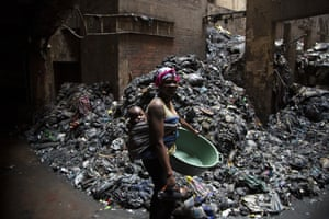 Johannesburg, South Africa. A woman passes a pile of rubbish outside the building where she lives in Hillbrow