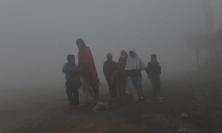 Pakistani children walk to school surrounded by heavy smog