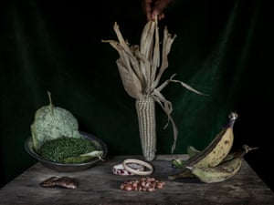 Table in Nadine Doko's house with food grown on her own plot of land – corn cob, bananas, thinly-sliced squash leaves, ground nuts – and handmade bracelets and a 'gris-gris' talisman to ward off evil.