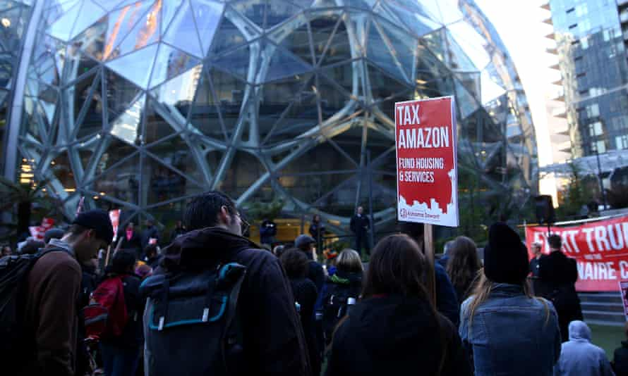 """People gather with """"Tax Amazon"""" signs in front of the Amazon Spheres in Seattle before the city council vote on Monday."""