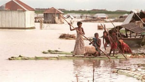 A family leaves their flooded home in Tangail, Bangladesh. 'In a crowded world subject to such adverse shifts of climate, who would take care of such greenhouse refugees?' says the film's narrator.