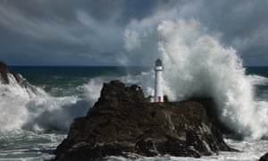 A lighthouse standing strong as waves and a storm crash around it.