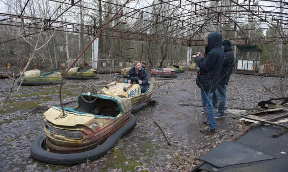 A man in a dilapidated bumper car with two onlookers, one with a camera, in Pripyat's decaying public park.