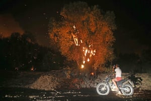 Muğla, Turkey A motorcyclist pauses to take photographs of a fire that broke out in a forest in the Dalaman district