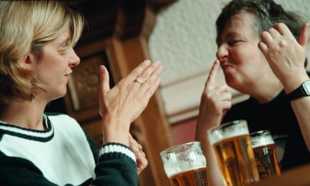 People in a pub drinking and using sign language.