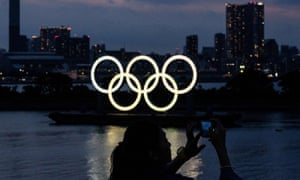 A woman takes pictures in front of the Olympic rings in Tokyo