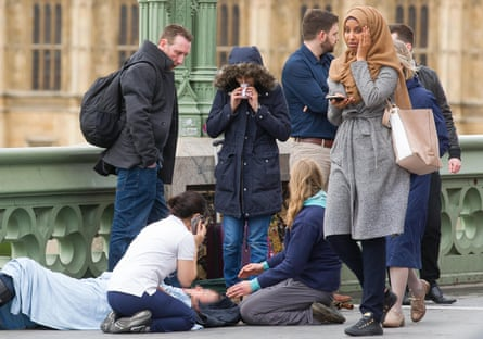 A second photo (above) shows the woman visibly distressed as she passes the scene of the attack on Westminster Bridge.