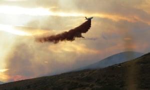 A plane drops fire retardant on a wildfire near Twisp