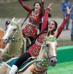 Riders in traditional dress perform stunts on horseback at the opening ceremony.